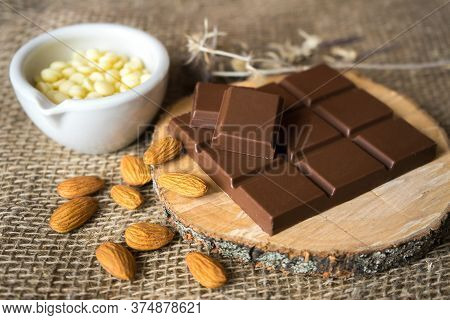 Chocolate With Cocoa Butter And Almonds On Wood