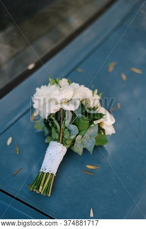 Bridal Bouquet Of White Peonies, Roses, Branches Of Eucalypt Tree And Lace Ribbon On The Hood Of The