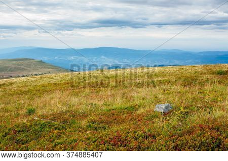 Meadow In Weathered Grass. Calm Mountain Landscape In Autumn. Stone On The Hill. Cloudy Weather