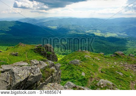 Rock On The Grassy Slope. Sunny Summer Landscape In Mountains. Ridge In The Distance. Clouds On The