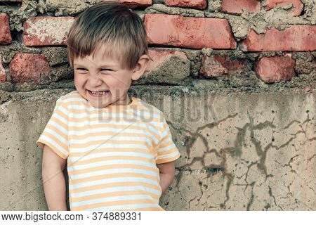 Portrait Of A Smiling 2 Years Old Boy On A Brick Wall Background. A Pretty Child Smiles And Looks Aw