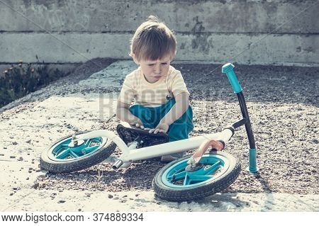 A Handsome Boy Of 2 Years Old Is Looking At A Bicycle Lying At His Feet. Child And Bike Without Peda