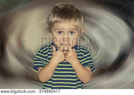 A Two-year-old Boy With Sad, Frightened, Guilty Eyes Put His Fingers In His Mouth On A Blurry Backgr