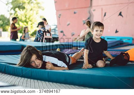 Happy Children Playing Lying On Trampoline. Brothers Are Having Fun Lying On A Sports Mat On A Tramp