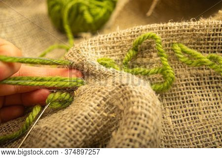 The Girl Stitches Together Pieces Of Coarse-textured Burlap With Green Threads. Close Up.