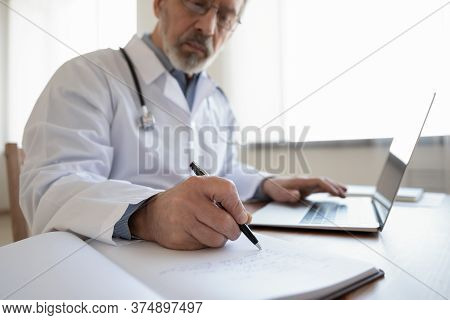 Elderly Male Doctor Fill Patient Anamnesis In Medical Journal
