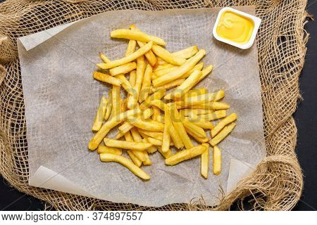 French Fries In A White Paper With Cheese Sauce Black Background. Top View, Eating Junk Food