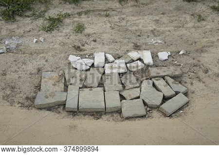 Hole In The Land Road Sealed With Old Bricks. Road Repair Concept