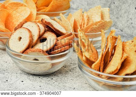 Potato And Corn Chips, Snacks, Crackers In Transparent Glass Plates And Sauces. Mix Of Snacks.