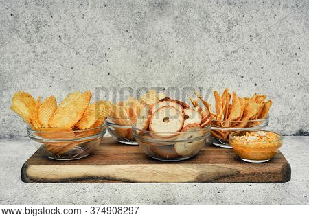 Mix Of Chips, Snacks And Crackers On A Wooden Stand. Unhealthy Food, Beer Snack, Ready Meal. Close U