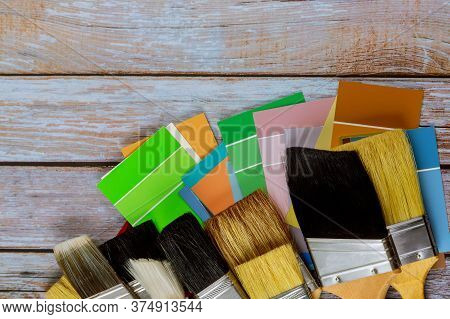 Professional Decorator Various Painting Tools With A Brush And Color Palette On Wooden Background