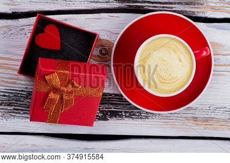 Cup Of Foamy Coffee And Opened Gift Box. Topview Flat Lay. Old White Wooden Background.