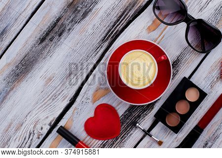 Flat Lay Coffee With Sunglasses And Makeup Accessories. Topview From Above. White Wooden Background.
