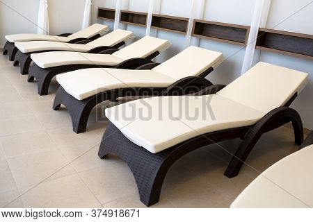 Deck Chairs In A Row For A Relaxation In A Spa Center.