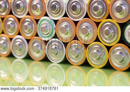 Multiple Used Aa Alkaline Batteries Are Seen Arranged In A Pile On A Reflective Green Surface. Close