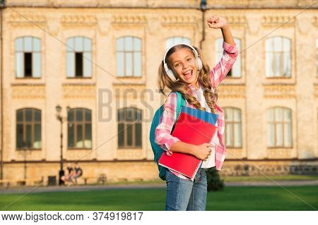 Small Girl With Book And Headset. Literature For Kids. Childhood Developing. Work With Notebook. Bac