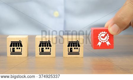 Close-up Hand Choose Quality Symbol On Cube Wooden Toy Blocks Stacked With Franchise Business Store