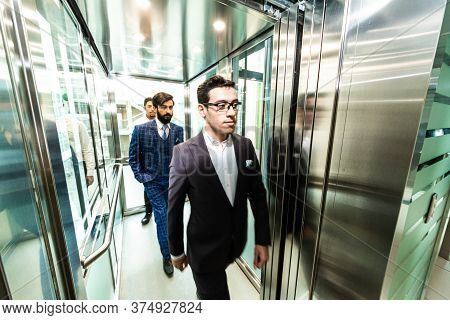 Business Team Group Going On Elevator. Business People In A Large Glass Elevator In A Modern Office.