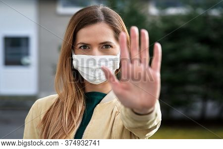 Young Woman Wearing White Cotton Virus Mouth Nose Mask, Holding Hand In Front Of Her As Stop Or Halt