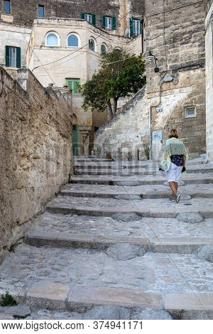 Matera, Italy - September 14, 2019: Woman During A Walk On Cobblestone Street In The Sassi Di Matera