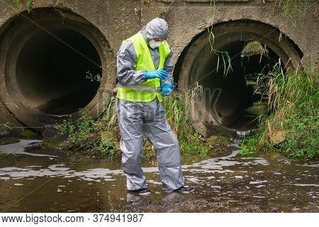 A Man In A Protective Suit And Mask Took A Soil Sample From The Bottom Of The River Into A Petri Dis