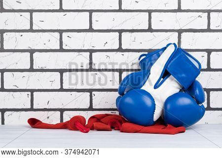 Blue Boxing Gloves Lie On Red Protective Bandages On A White Brick Background