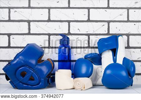 Blue Set Of Helmet And Boxing Gloves For Sports On A Brick Wall Background