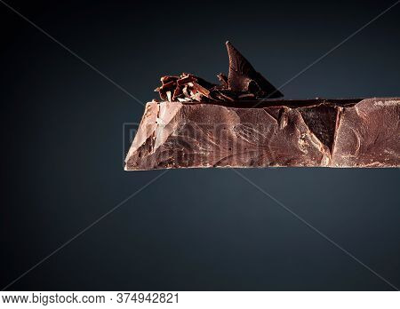 Large Piece Of Dark Chocolate And  Chocolate Crumbs On A Black Background. Copy Space.