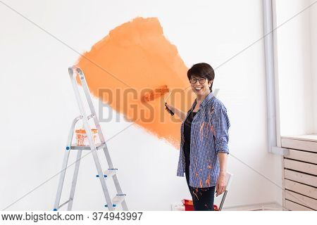Happy Middle-aged Woman Painting Wall In Her New Apartment. Renovation, Redecoration And Repair Conc