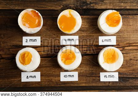 Different Cooking Time And Readiness Stages Of Boiled Chicken Eggs On Wooden Table, Flat Lay