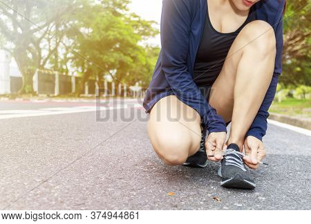 Close Up Of Young Woman Runner Tying Laces Her Shoelaces.  Hands Asian Women Tying Her Black Shoe.
