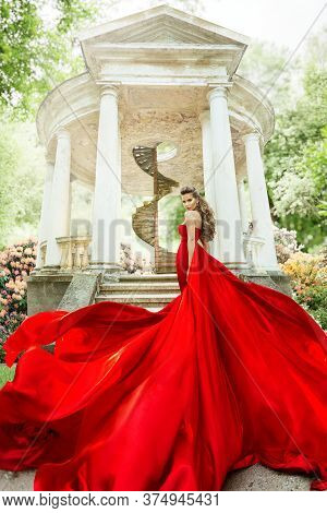 Fashion Model Waving Long Fluttering Red Dress, Woman In Garden, Old White Alcove In Flowers, Outdoo