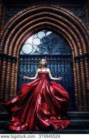 Fashion Model Near Medieval Castle Gate Door, Woman Beauty Glamour Portrait In Elegant Waving Red Dr
