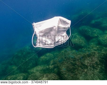 People Throws Out A Medical Face Mask Floating Underwater On Ocean Water
