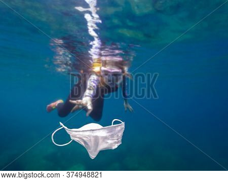 Volunteer Girl Snorkeling With Swimsuit And Picking Up A Mask Garbage On Ocean
