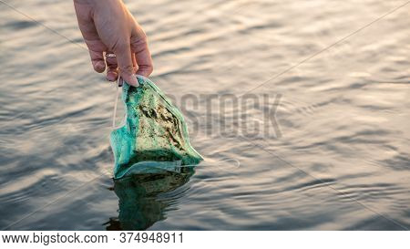 Woman Hand Picking Up Discarded Used Disposable Medical Mask In Sea Waters