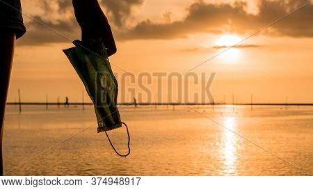 Woman Hand Holding Medical Mask On Beach With Beautiful Sunset Light. Covid19