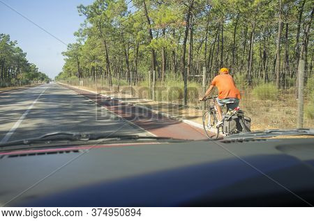 Driving Slowly Behind One Cyclist At Forest Road. View From The Inside Of The Car