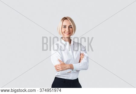 Beautiful Businesswoman In Formalwear Standing With Crossed Arms On Light Studio Background