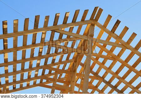 Yellow Wooden Rafters Against The Blue Sky. Bright Background On The Topic Of Construction And Repai