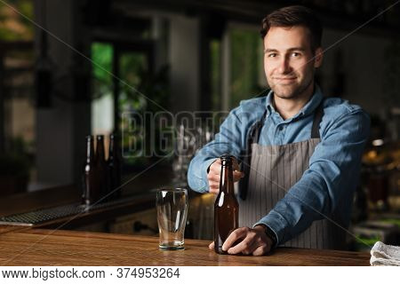Craft Beer For Client. Smiling Bartender Using Opener, Opens Bottle Of Beer, Near Empty Glass In Int