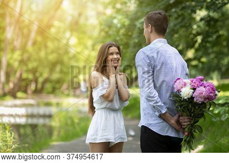 Affectionate Boyfriend Hiding Bouquet Of Flowers For His Beloved Girlfriend Behind His Back At Park,