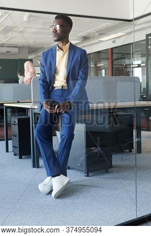 Vertical Full Length Portrait Of Successful African-american Businessman Looking Away While Leaning