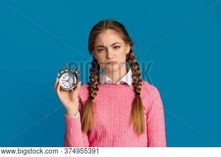 Oversleep Concept. Tired Teenager Girl With Pigtails Holds Alarm Clock In Her Hands Isolated On Blue