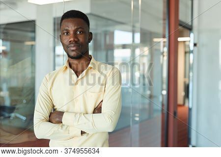 Waist Up Portrait Of Young African-american Businessman Wearing Yellow Shirt Posing Confidently And