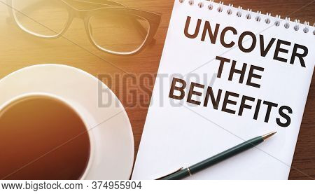 Uncover The Benefits - Text Written On Notebook On Wooden Table With Pen Coffee And Glasses
