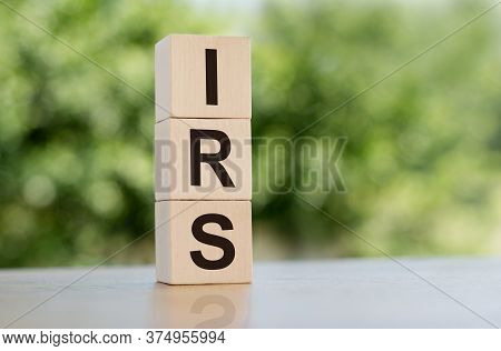 Irs Word Written On Wooden Cubes On Table With Green Background