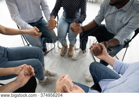 People Sitting In Circle Holding Hands Involved At Group Therapy