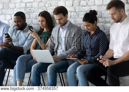 Multiracial Applicants Focused In Gadgets While Await For Job Interview