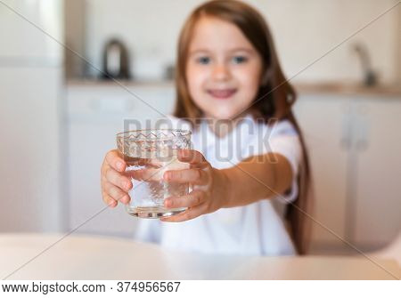Hydration. Cute Girl Showing Glass Of Mineral Water Drinking Healthy Liquid Sitting In Kitchen Indoo